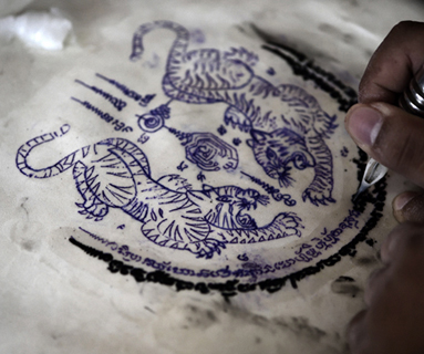 Tattoo being applied to parchment skin.